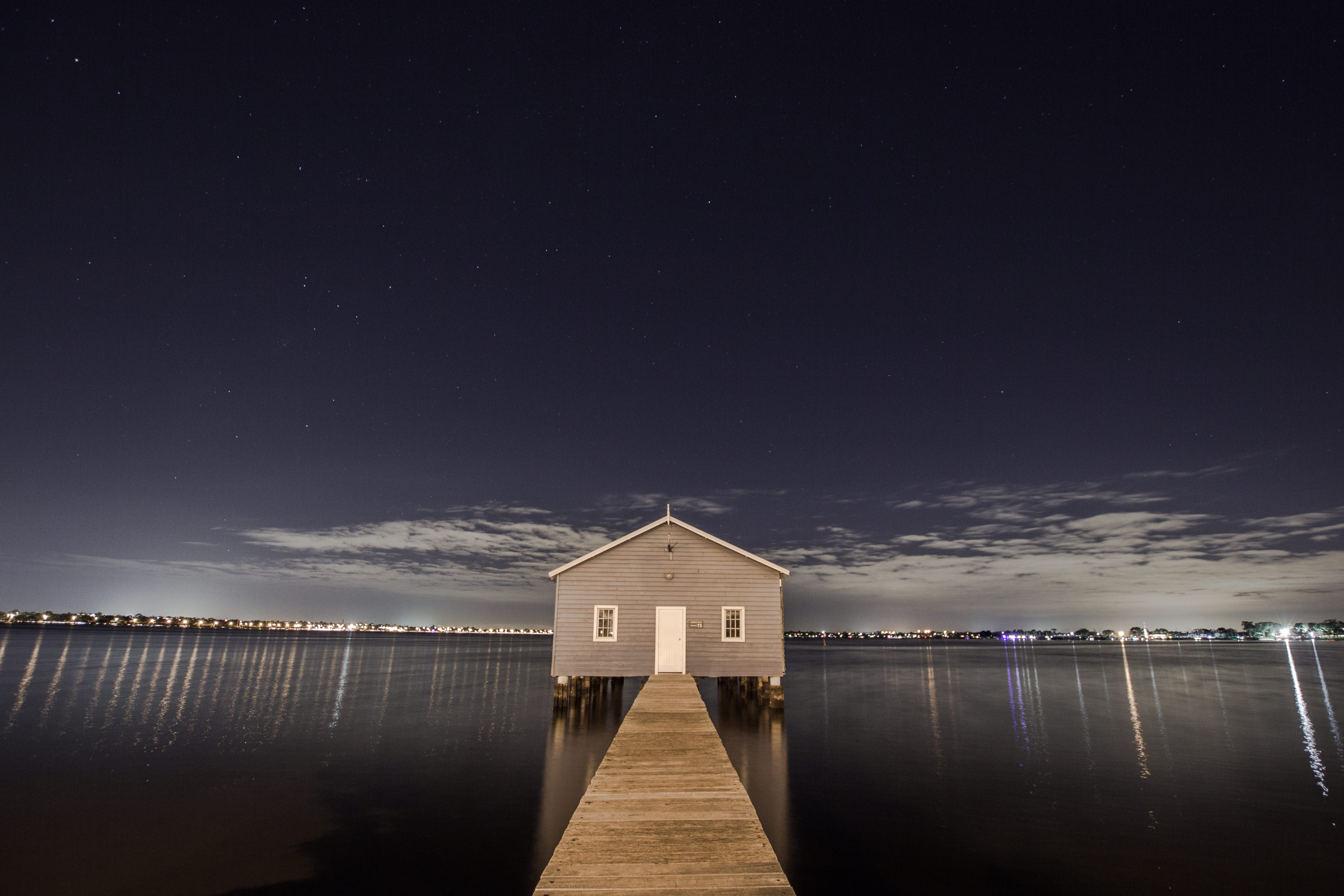 Photo of a wooden shed on the end of a pier, at night, over calm water.