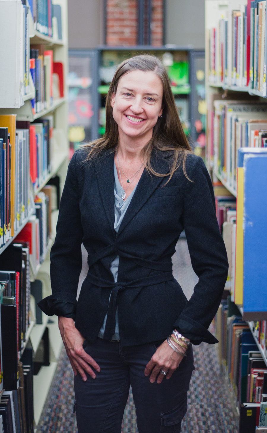 A photo of a white woman with shoulder length light brown hair. She is wearing a black sport coat.