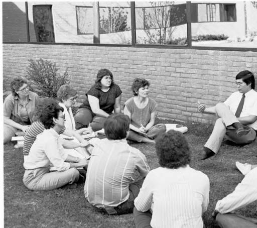 Class Meeting Outside, 1987. Group of students sitting in a circle on the groud.