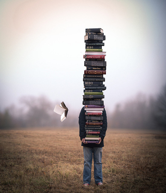 A child holding a very large stack of books