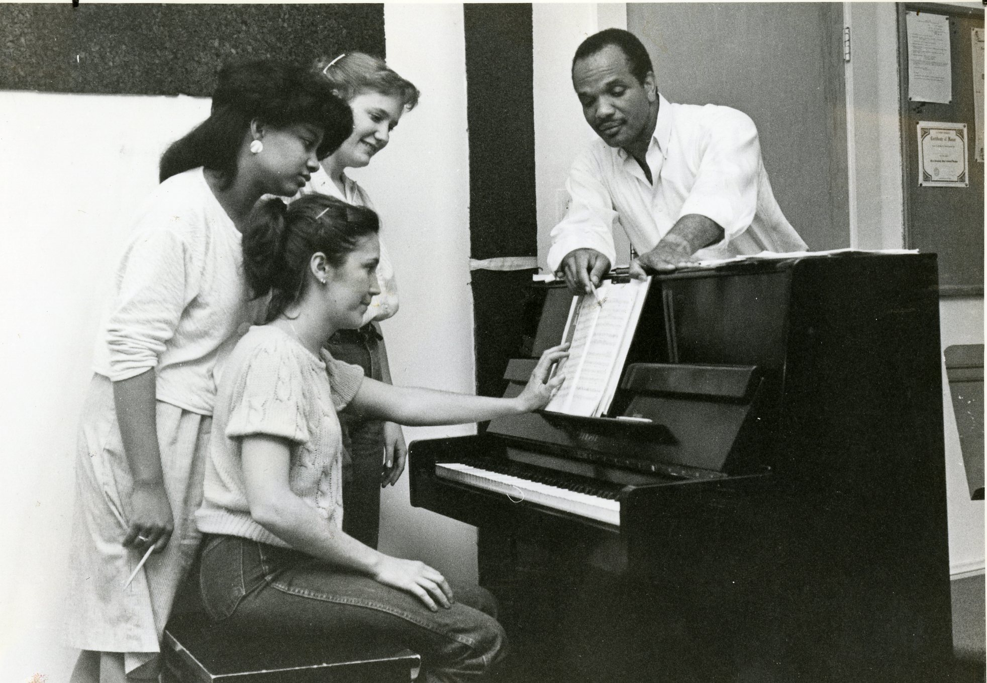 Archive shot of male music teacher helping female students