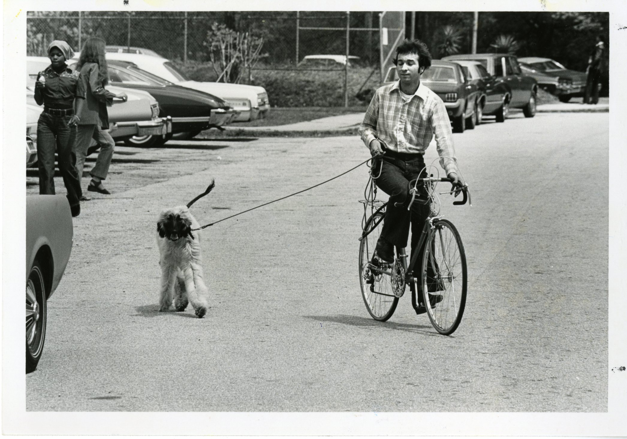 Archive shot of a student on a bike with a dog