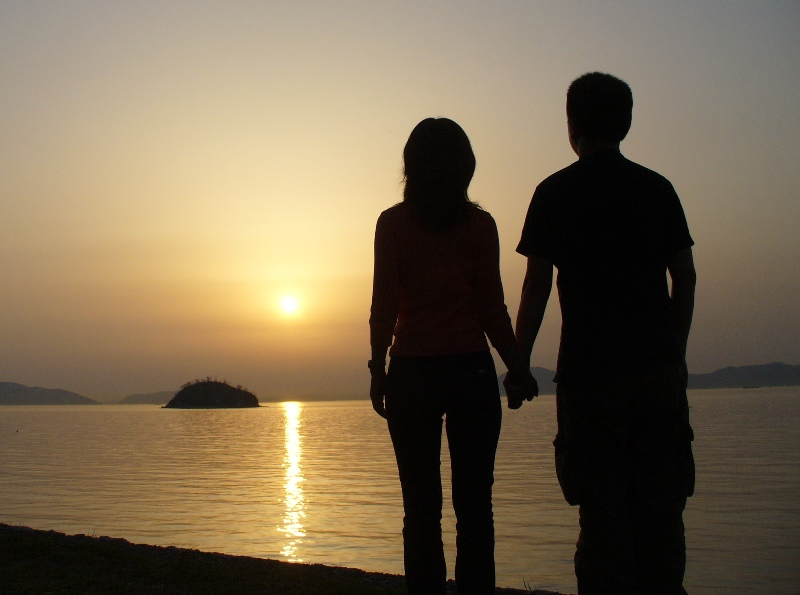 Silhouette of boy and girl holding hands at the beach
