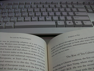 Photo of an open book next to a computer keyboard