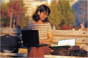 Woman on a park bench holding a computer and looking at a book
