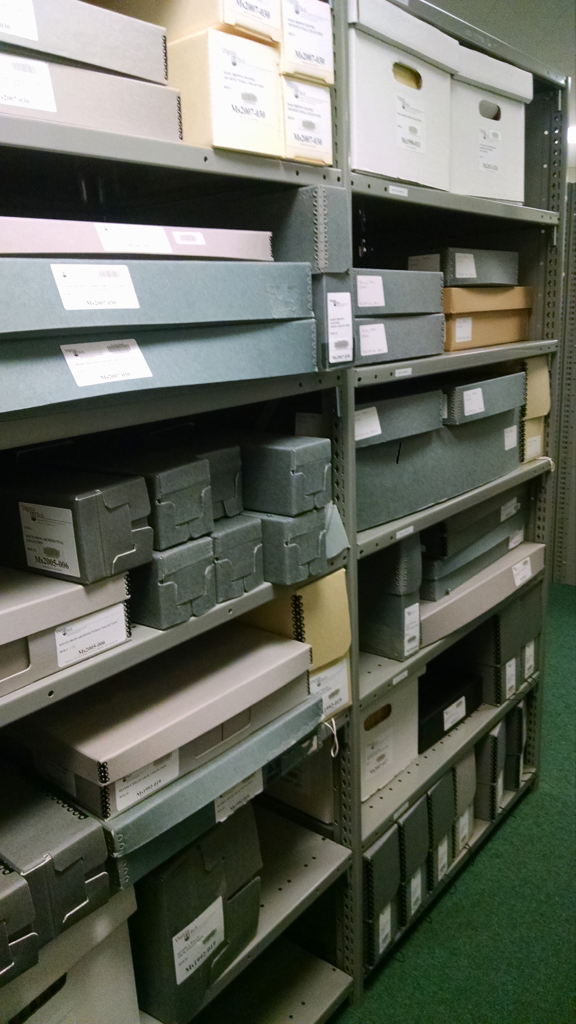 Perspective view of 6 foot archival shelves with many boxes of different colors and sizes.