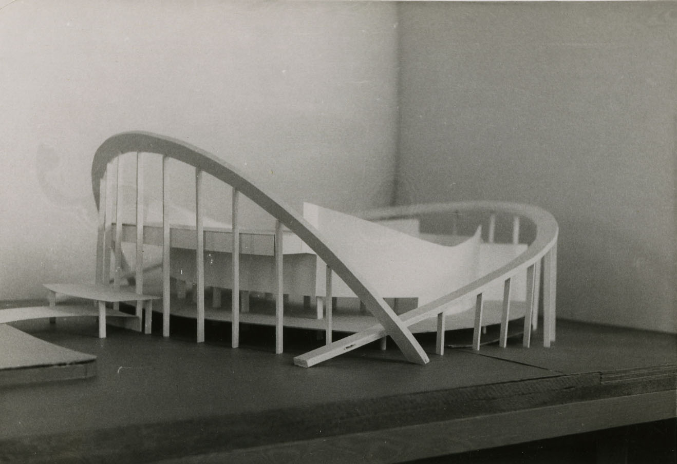 Black and white photograph of architectural model on table, side perspective.