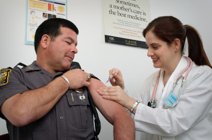 Image of nurse providing a vaccine to a law enforcement officer