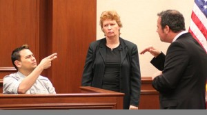 The image shows a deaf man answering a lawyer's questions and an interpreter in black standing by.