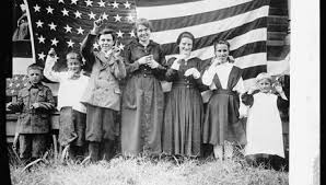 The image is from the U.S. National Archives and shows a teacher and children in front of an American flag signing.
