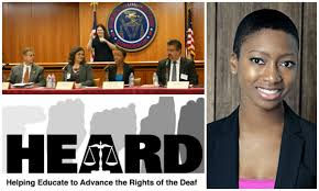 This is a picture of HEARD, an advocacy organization for Deaf prisoners. It shows the FCC panel behind a table in the court room and an interpreter behind them. On the right is the African American founder, Talila A. Lewis. She has short hair and is wearing a black jacket over a shocking pink top.