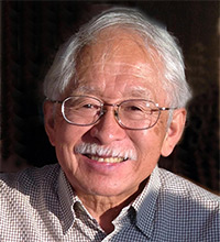 Photograph of Ron Hirano. He has white hair, a moustache, and is wearing glasses.