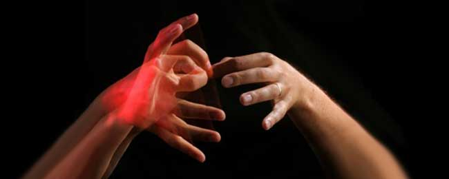 "The photo is from an article and shows two hands signing ""interpreting"" against a black background"