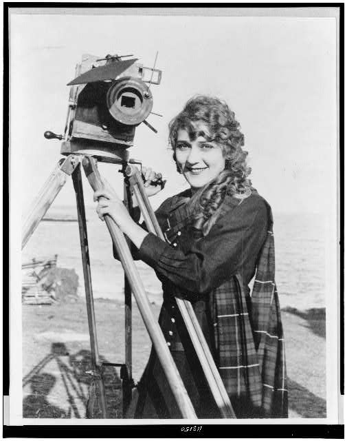 [Mary Pickford, half-length portrait, standing, facing slightly left, with motion picture camera, on beach]