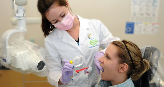 Picture of a dentist examining a young girl's teeth