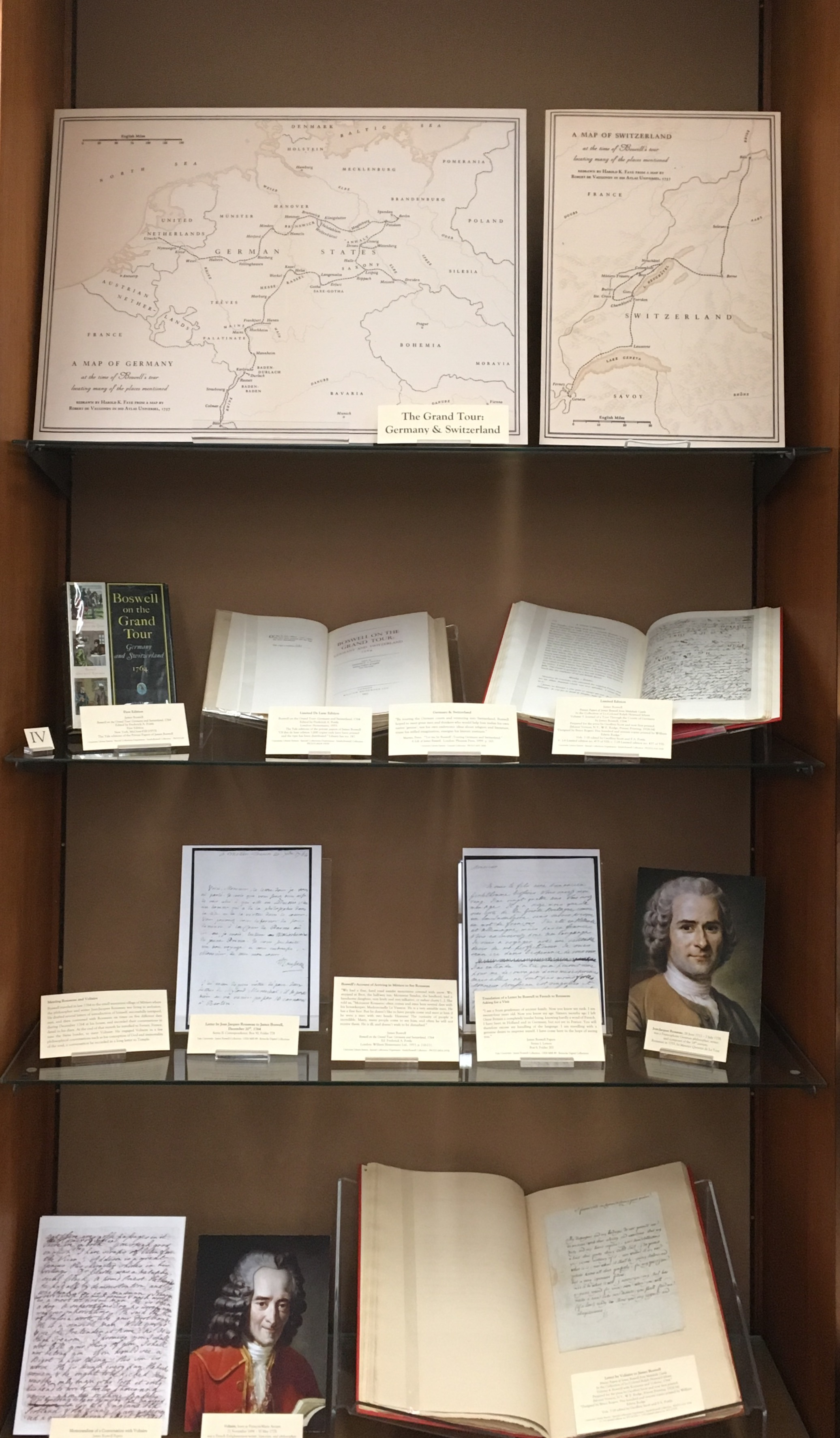 A display case featuring maps of Germany and Holland and the books, supplementary texts, and images featured on this page.