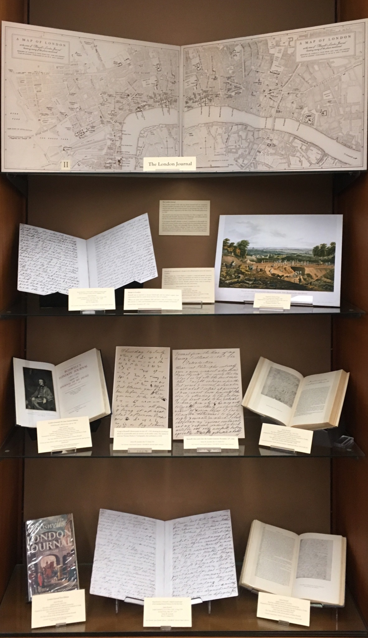 A display case featuring a large, two-paneled map of London and the books, supplementary texts, and images featured on this page.