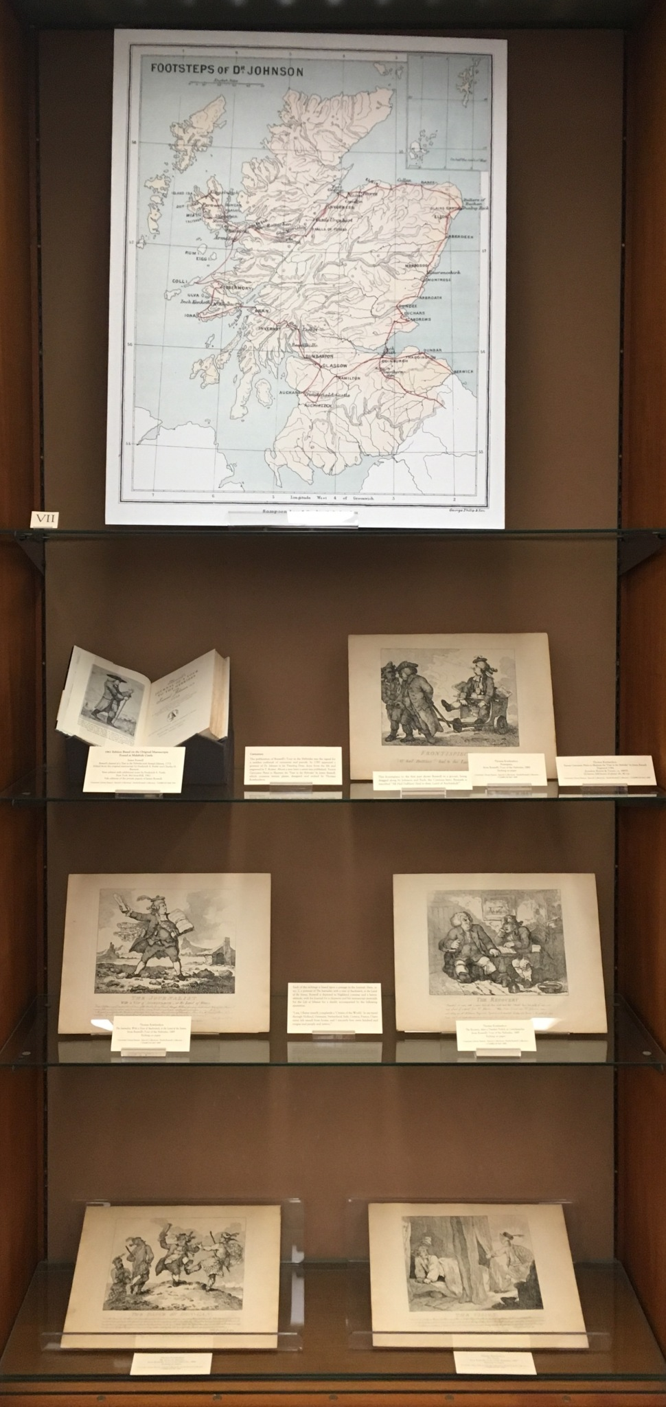 A display case featuring a large map of Scotland and the books, supplementary texts, and images featured on this page.