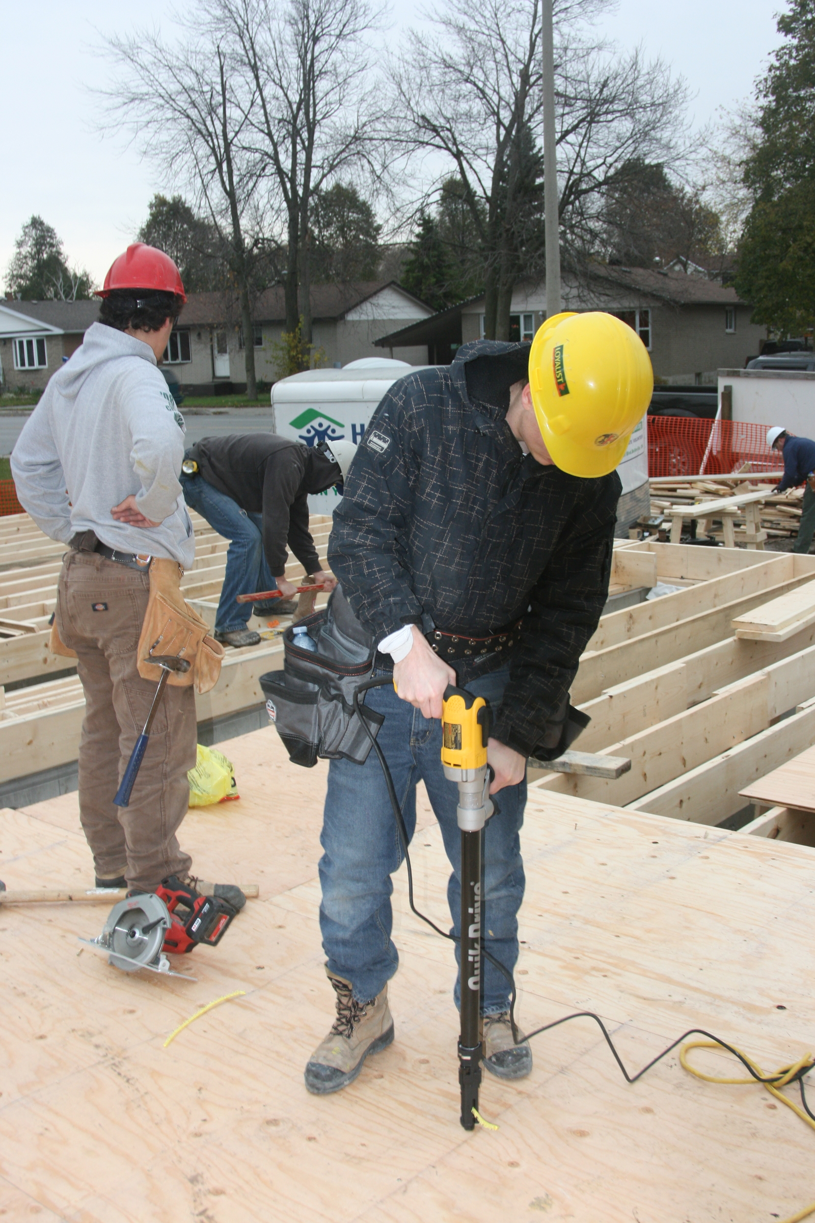 Three students in hardhats install a wooden floor in a home on a construction site.