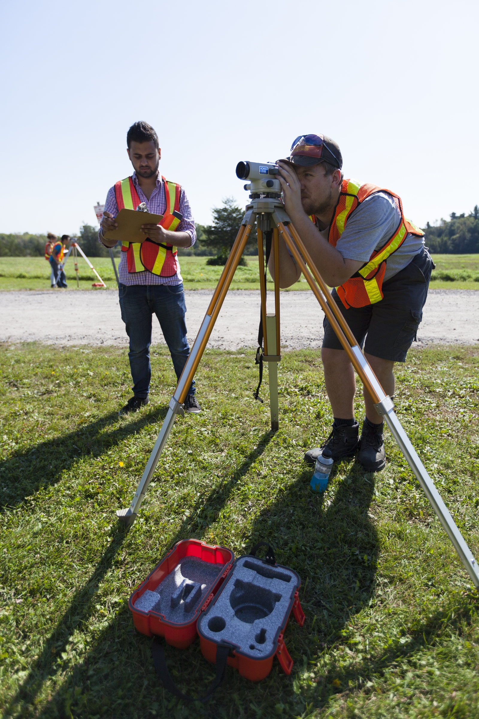 Two students in safety vests stand in a field. One looks through a land survey instrument, and the other writes notes.