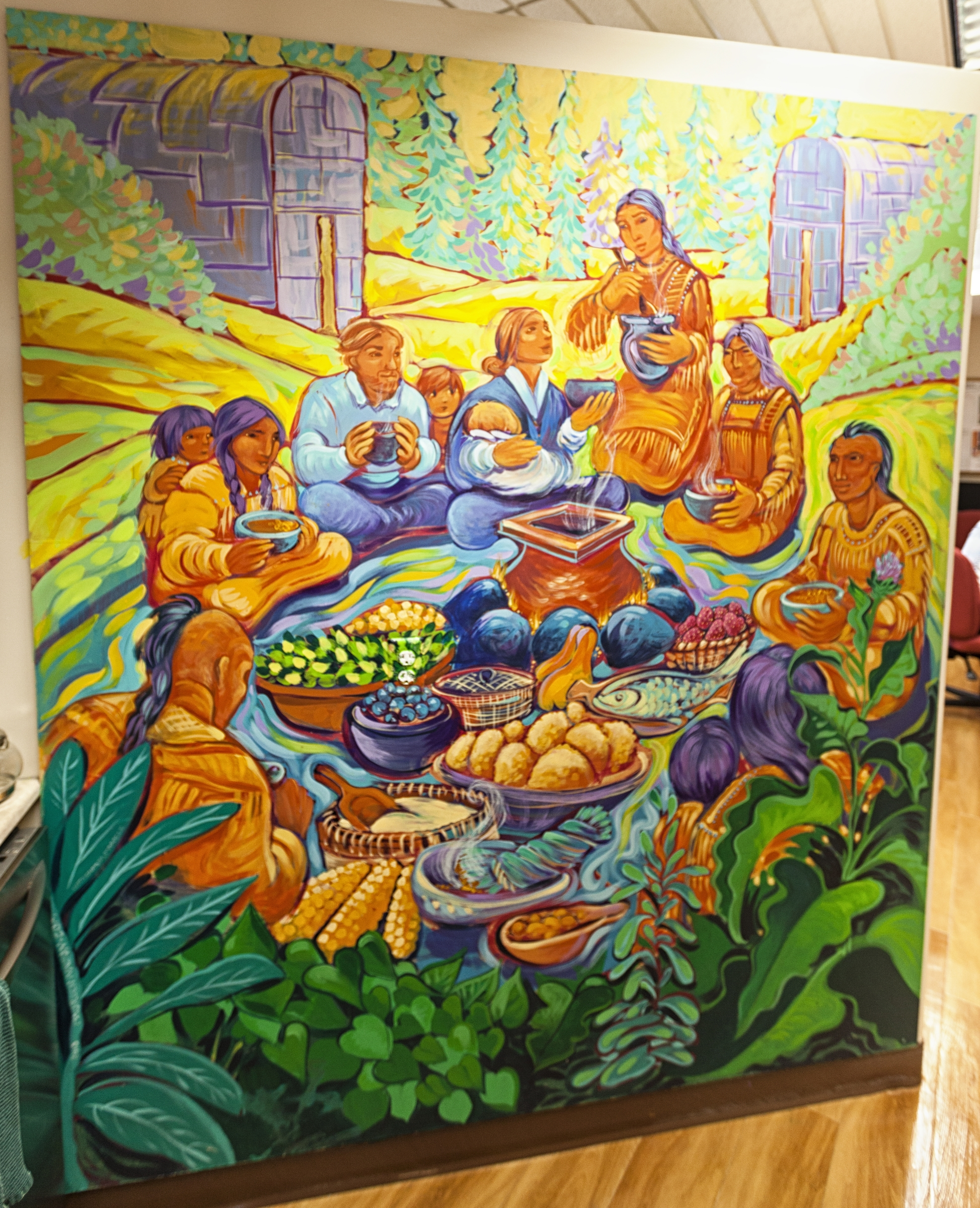 A colourful painting of a group of Indigenous people and a group of settlers sharing a meal together. They sit in a circle on green grass, surrounded by trees. Longhouses stand in the background.
