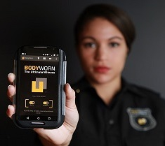 "Law enforcement or security officer holds out a device with the word ""Bodyworn"" visible on the screen."