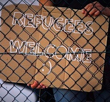 "Cardboard sign saying ""Refugees Welcome"" with smiley face emoji"