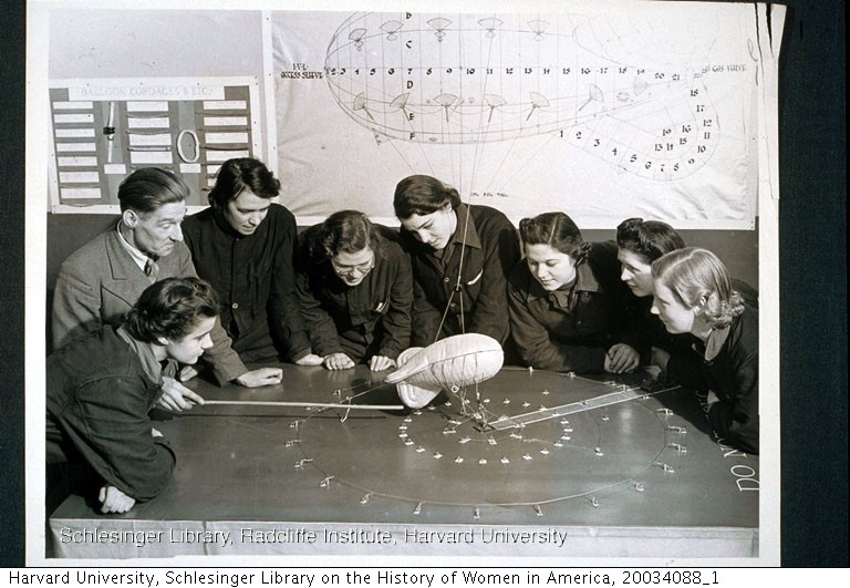 Members of the Women's Auxiliary Air Force gathered around a table while a Royal Air Force instructor demonstrates a model balloon. The women are training to become barrage balloon operators.