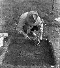 Man wearing a hat and excavating an archaeological dig site.