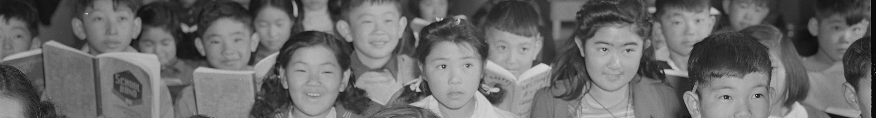 A photo of Japanese American children facing the camera with books open during a grammar lesson