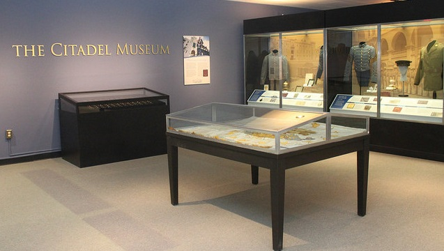 Interior of Citadel Museum showing alumni ring display case and 3 19th and 20th century cadet uniforms