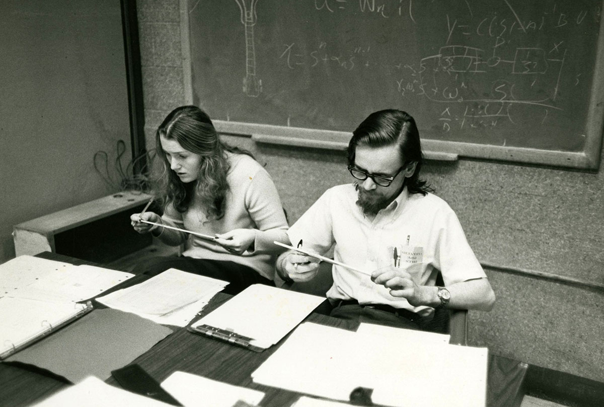 Female and male student with slide rules, Civil Engineering, 1970s.