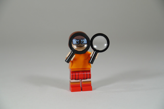 Photo of Lego figurine in orange holding two tilted magnifying glasses.