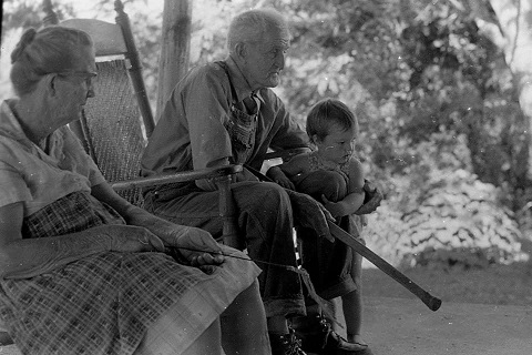 Dr. Crisp, aged about 18 months, on the porch with her great-grandparents near the coal mines in Brilliant, Alabama