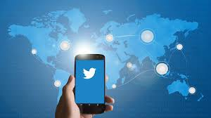 Cellphone with Twitter bird displayed on background of world map