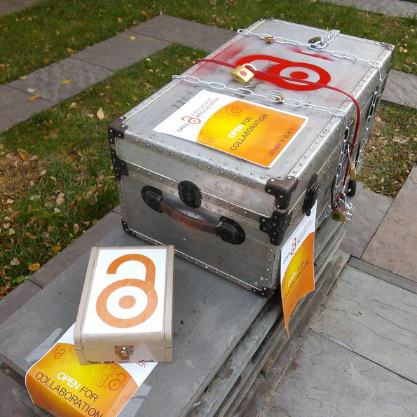 A photo of a locked metal trunk used for Open Access Week 2015. The silver trunk has a closed red lock spraypainted on it and is covered with chains and padlocks and signs for open access week.