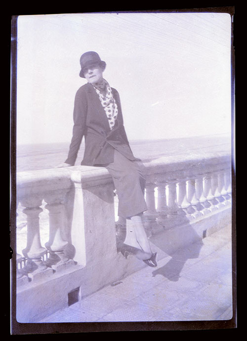 Unidentified woman sitting on wall by ocean, same location as Series VII, 1.118, wearing hat and polka dot blouse, circa 1926-1931, negative