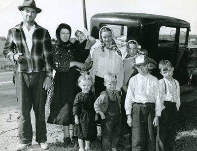 Black and white photograph of an immigrant family standing in front of a car.