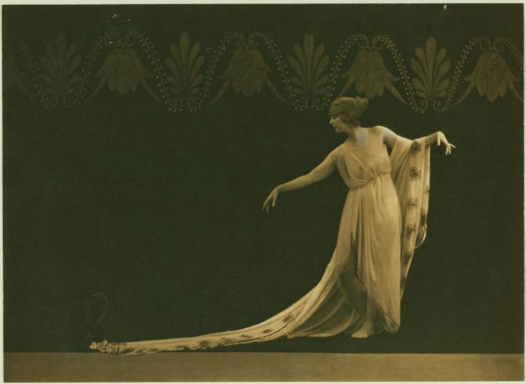 Sepia-toned image of Ruth St. Denis posing in Greek dress with a long veil