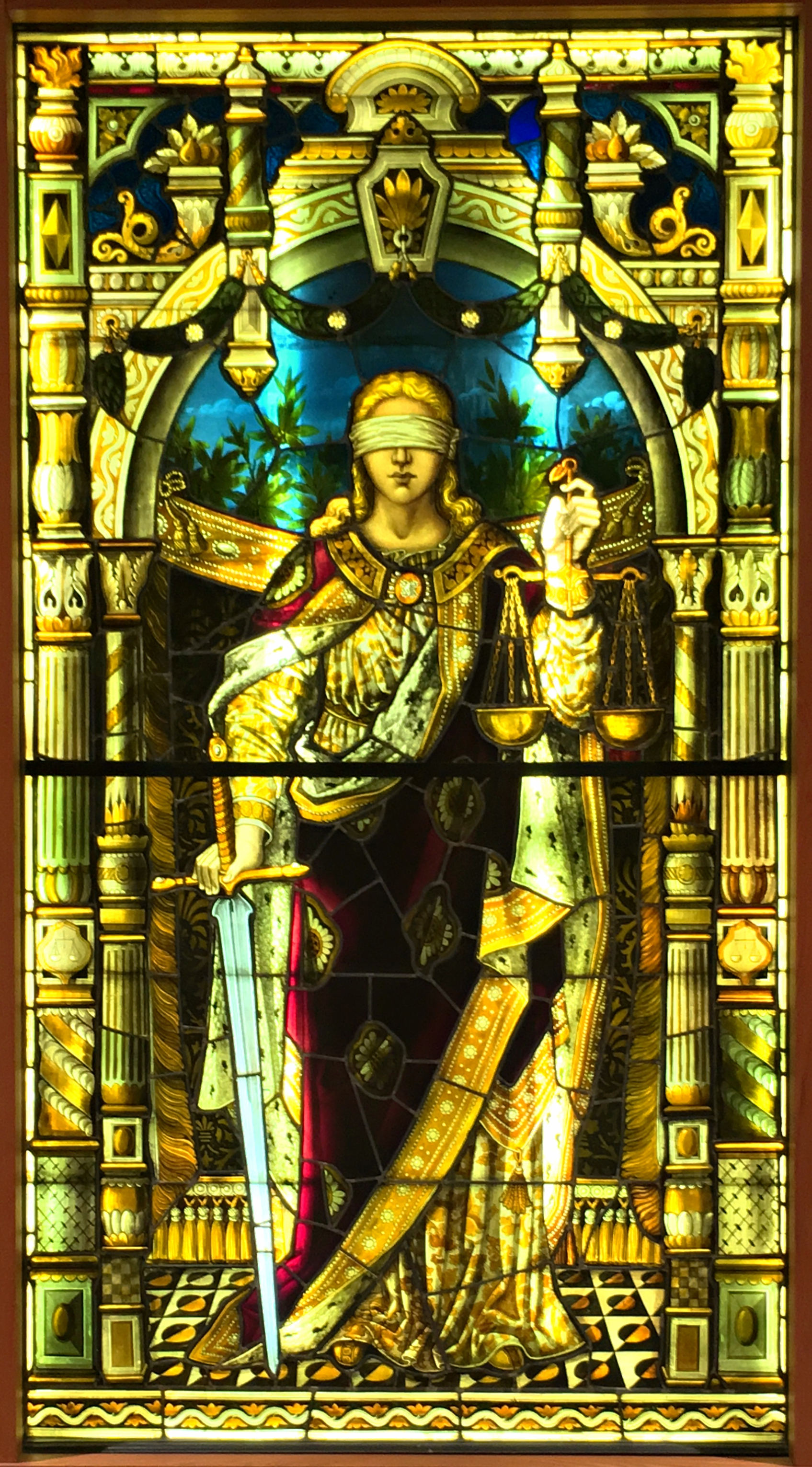 An image of the stained glass window of Lady Justice on display outside the E.K. Williams Law Library.
