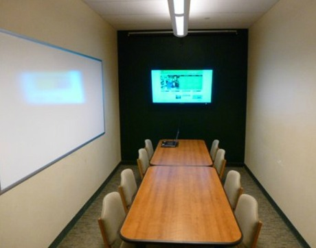 An image of a study room with eight chairs, two tables, a whiteboard, and a television.