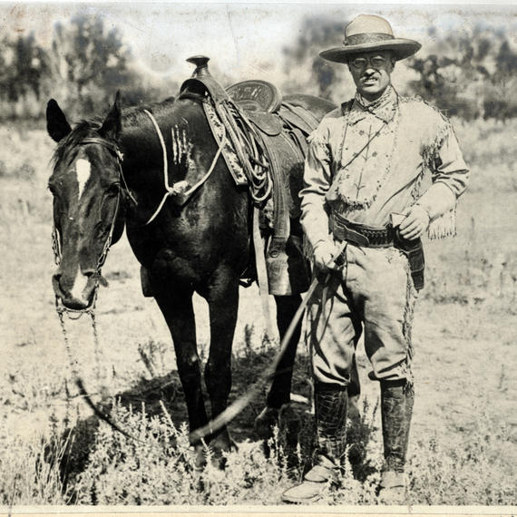 T. Roosevelt wearing a uniform standing next to a black horse