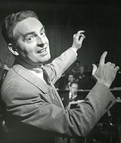 Image of Fred Waring with hands rasied to conduct musicians in the background.
