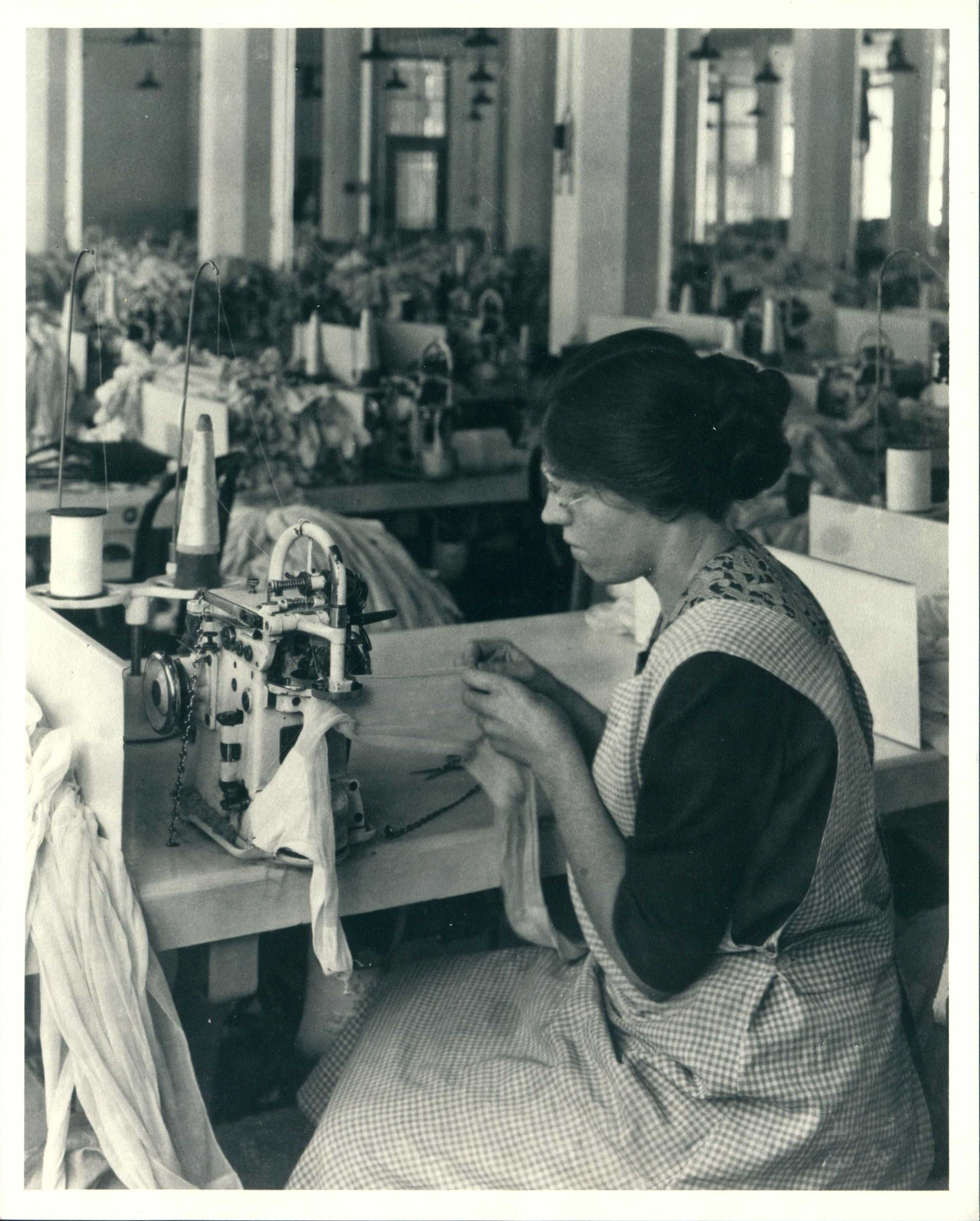 Woman in factory sitting at sewing machine seaming knit stockings.