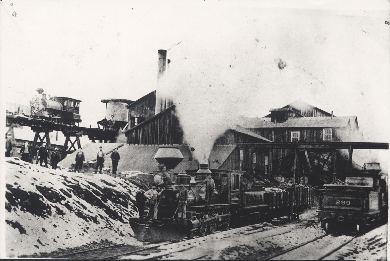 Wooden structure of iron works with locomotives on tracks in the foreground and a locomotive on a wooden trestle emerging from the back of the iron works. Workmen standing along the side of the works and on the locomotive in the foreground.