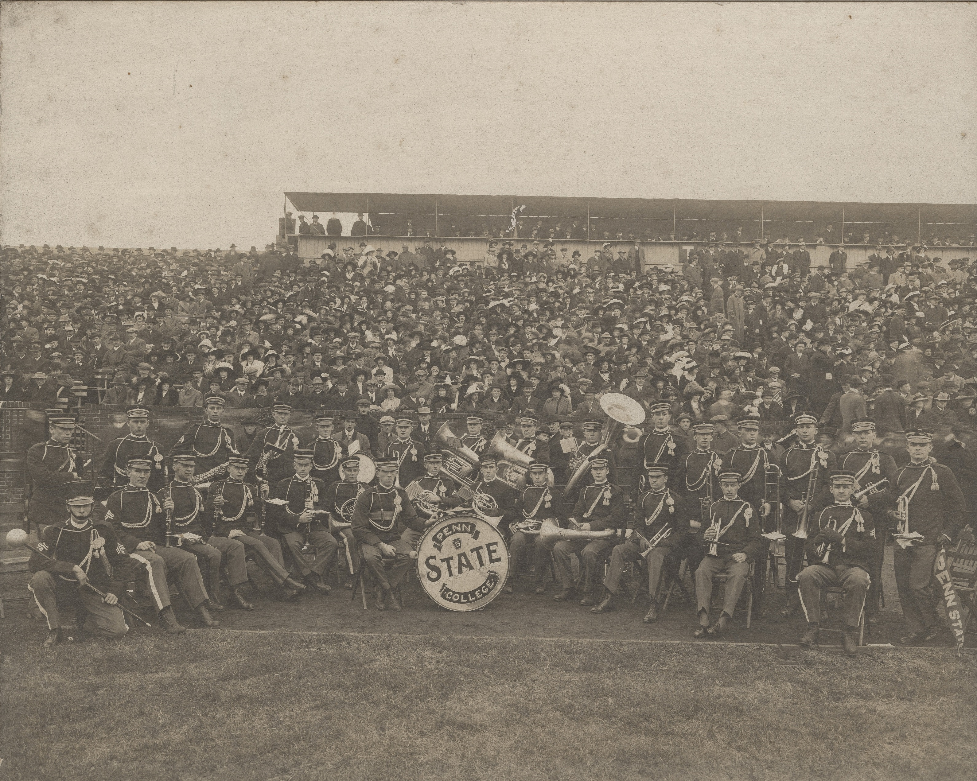 small marching band in uniform sitting in front of a stadium crowd
