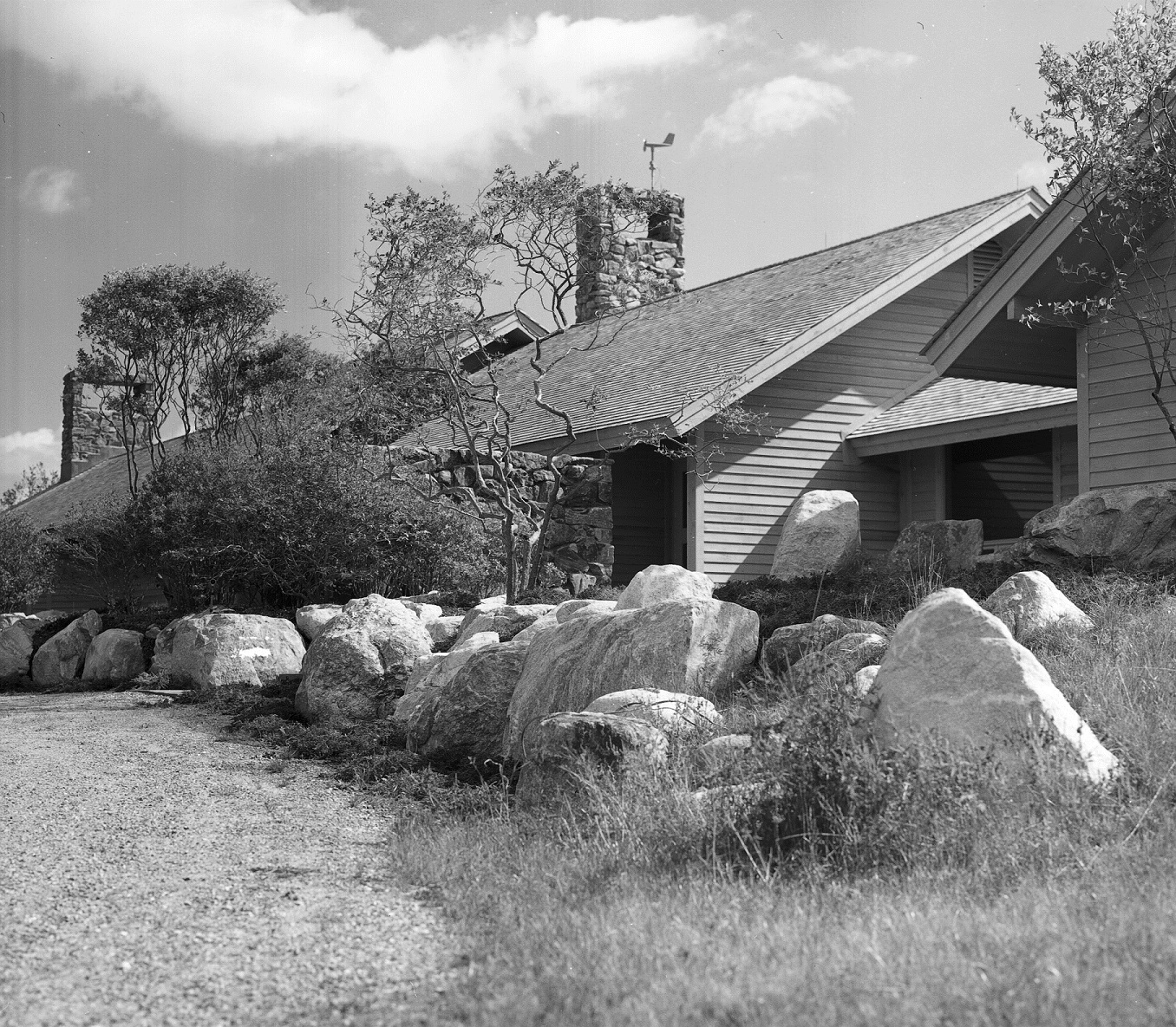 driveway leading to a house with trees and large boulders arranged in front of it
