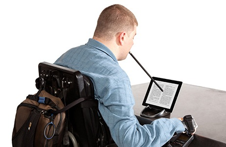 Person in a wheelchair using a mouse stick to use a tablet