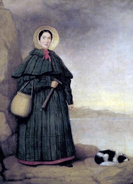 Portrait of Mary Anning circa 1842, wearing a bonnet and a grey coat.  She is on the shore and her black and white dog, Tray, lays beside her.