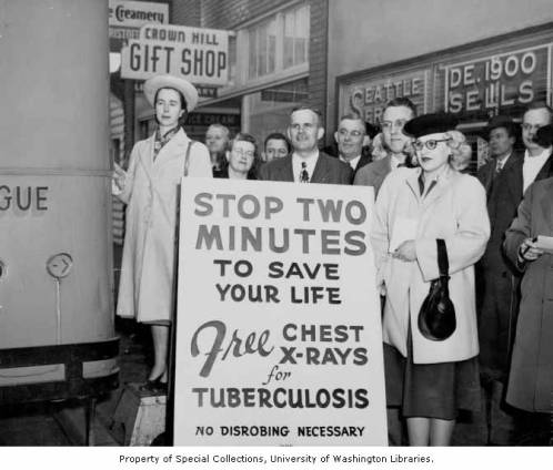 Crowd standing by sign advertising free chest x-ray screening on Crown Hill, Seattle, ca. 1955